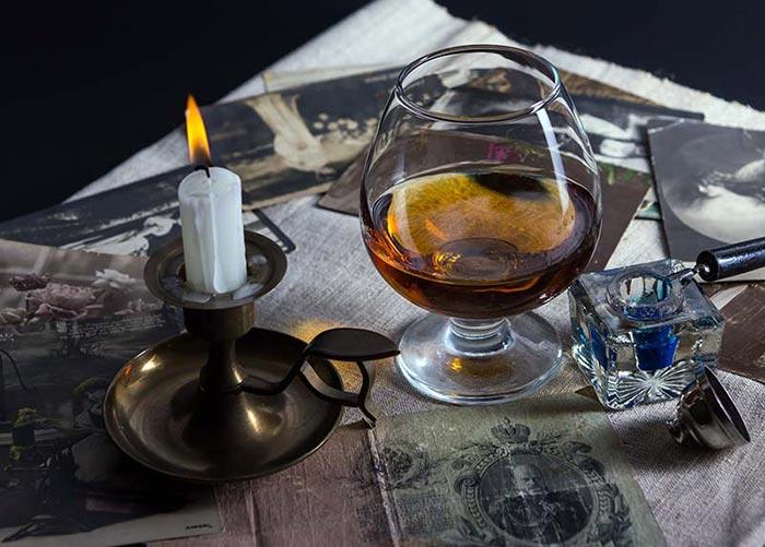 Фото коньяка в стакане и свеча на столе